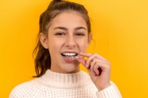 a girl using braces as part of her dental care routine