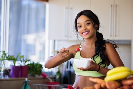 A woman holding a bowl of fruit