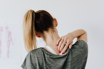 a woman experiencing neck pain after a workout