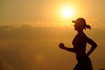 Silhouette of a woman jogging at dusk